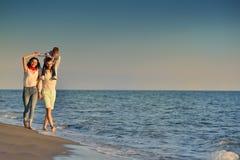 La jeune famille heureuse ont l'amusement sur la plage courue et sautent au coucher du soleil Image stock