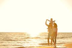 La jeune famille heureuse ont l'amusement sur la plage courue et sautent au coucher du soleil Photographie stock libre de droits