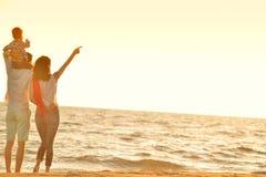 La jeune famille heureuse ont l'amusement sur la plage courue et sautent au coucher du soleil Image libre de droits