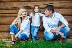 La jeune famille heureuse s'assied près de la maison en bois Photos stock