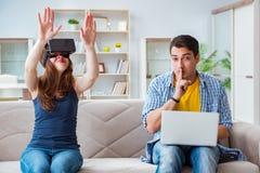 La jeune famille jouant des jeux avec des verres de réalité virtuelle Photographie stock libre de droits