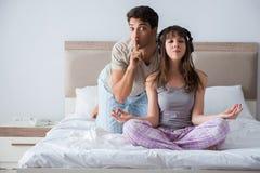 La jeune famille méditant dans la chambre à coucher de lit Image libre de droits