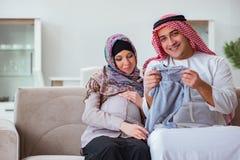 La jeune famille musulmane arabe avec l'épouse enceinte attendant le bébé Photographie stock