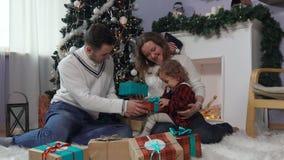 La jeune famille ouvre des cadeaux de Noël banque de vidéos