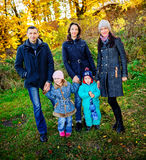 La jeune famille, parents avec de petits enfants dans la ville d'or d'automne se garent Images libres de droits