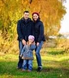 La jeune famille, parents avec de petits enfants dans la ville d'or d'automne se garent Image libre de droits