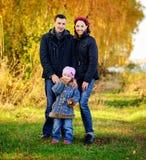 La jeune famille, parents avec de petits enfants dans la ville d'or d'automne se garent Image stock