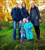 La jeune famille, parents avec de petits enfants dans la ville d'or d'automne se garent Photographie stock
