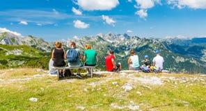 La jeune famille sur la montagne regarde à la colline lointaine Montagne Vogel, Triglav de la Slovénie et près de lac Bohinj photographie stock