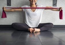 La jeune femelle active de sourire employant un theraband exercent la bande pour renforcer ses muscles de bras dans le studio photographie stock
