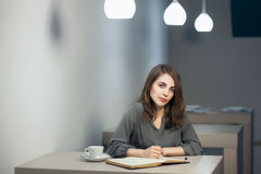 La jeune femelle adulte a la pause-café dans des notes de café et d'écriture en journal intime ou bloc-notes ; Photographie stock libre de droits