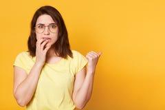 La jeune femelle attirante effrayée tient ses doigts sur des lèvres, expositions de côté avec le pouce, sembler effrayé Le modèle photos libres de droits