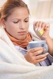 La jeune femelle a attrapé le mauvais potable froid de sensation de thé images stock