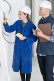 La jeune femelle commerce la prise de câblage d'apprenti Image libre de droits