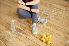 La jeune femelle de sport au gymnase faisant une pause de séance d'entraînement et l'haltère ont été placées tout près photographie stock