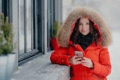 La jeune femelle européenne de sourire dans le manteau rouge, a la manucure noire, utilise l'instrument électronique moderne pour image stock