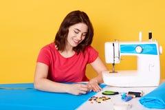 La jeune femelle gaie inspirée écrit avec la craie sur le morceau bleu de tissu, faisant le modèle pour le nouvel article des vêt photos stock