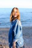 La jeune femelle heureuse développe des cheveux et pose sur l'appareil-photo, o debout Images libres de droits
