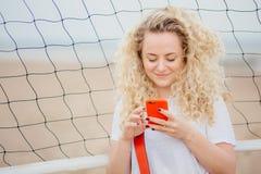 La jeune femelle a le téléphone intelligent moderne de prises de cheveux bouclés, télécharge des photos des réseaux sociaux, pose image libre de droits
