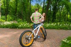 La jeune femelle regarde d'un type après avoir fait du vélo en parc photo libre de droits