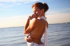 La jeune femelle s'est habillée, se tenant sur une plage de matin photographie stock libre de droits