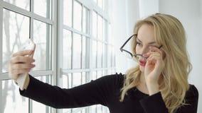 La jeune femme à la fenêtre prend des photos d'elle-même au téléphone avec l'appareil-photo avant image stock