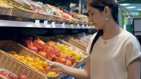 La jeune femme à l'épicerie choisit des légumes banque de vidéos