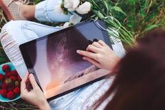 La jeune femme à l'aide d'un PC de comprimé se reposant dans l'herbe d'été avec le bouquet des pivoines fleurit Vacances d'été Photographie stock libre de droits