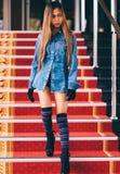 La jeune femme à la mode dans des blues-jean, et le long genou rayé cogne la marche vers le bas sur des escaliers avec le tapis r Photographie stock
