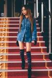 La jeune femme à la mode dans des blues-jean, et le long genou rayé cogne la marche vers le bas sur des escaliers avec le tapis r Photos stock
