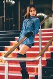 La jeune femme à la mode dans des blues-jean, et le long genou rayé cogne la marche vers le bas sur des escaliers avec le tapis r Image stock