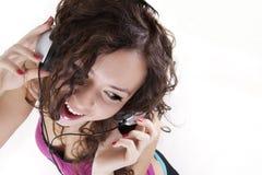 La jeune femme écoute la musique dans des écouteurs Image stock