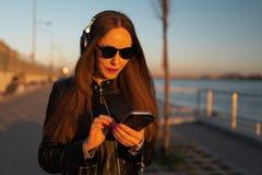 La jeune femme écoute la musique dans des écouteurs fermés par son téléphone presque utilisant une veste en cuir et des jean photo stock