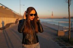 La jeune femme écoute la musique dans des écouteurs fermés par son téléphone presque utilisant une veste en cuir et des jean photo libre de droits