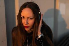 La jeune femme écoute la musique dans des écouteurs fermés par son téléphone presque utilisant une veste en cuir et des jean images libres de droits