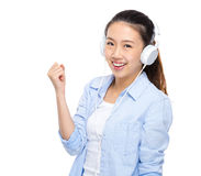 La jeune femme écoutent la musique par l'écouteur Images libres de droits