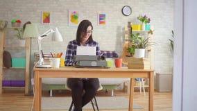 La jeune femme écrit sur une vieille machine à écrire banque de vidéos