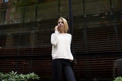 La jeune femme élégante arrêtée devant les grandes fenêtres du restaurant est chère, attendant son ami Image stock