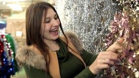 La jeune femme élégante attirante choisit le décor de Noël pour décorer un arbre de Noël Projectile de plan rapproché banque de vidéos