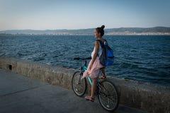 La jeune femme élégante dans la robe et avec le sac à dos monte la bicyclette sur la promenade Photo stock