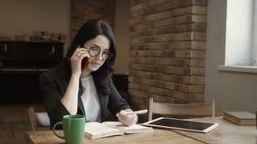 La jeune femme élégante utilisant des lunettes parle par le téléphone banque de vidéos