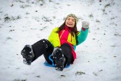 La jeune femme abaisse gaiement d'une colline sur le traîneau de soucoupe photos libres de droits