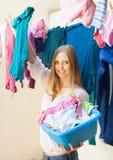 La jeune femme accroche des vêtements pour sécher images stock