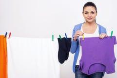 La jeune femme accroche des vêtements sur le dessiccateur pour des vêtements après lavage photographie stock libre de droits