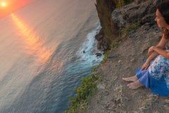 La jeune femme admire le coucher du soleil, Bali, Indonésie Photographie stock libre de droits