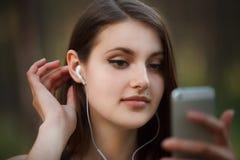 La jeune femme adolescente écoutent la musique sur son smartphone en Cl de parc Images libres de droits