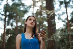 La jeune femme adolescente écoutent la musique sur son smartphone en parc Image stock