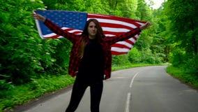 La jeune femme adolescente ondulant un drapeau des USA est patinage de rouleau par des bois Mouvement lent clips vidéos