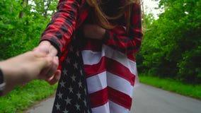 La jeune femme adolescente ondulant un drapeau des USA est patinage de rouleau sur la route rurale banque de vidéos
