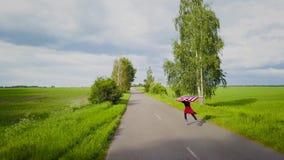 La jeune femme adolescente ondulant un drapeau des USA est patinage de rouleau sur la route rurale clips vidéos